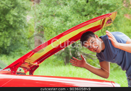 Lost handsome man checking his car engine stock photo, Lost handsome man checking his car engine after breaking down by Wavebreak Media