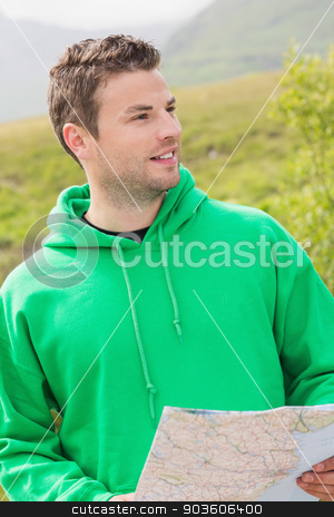 Athletic man holding a map and looking ahead stock photo, Athletic man holding a map and looking ahead in the countryside by Wavebreak Media