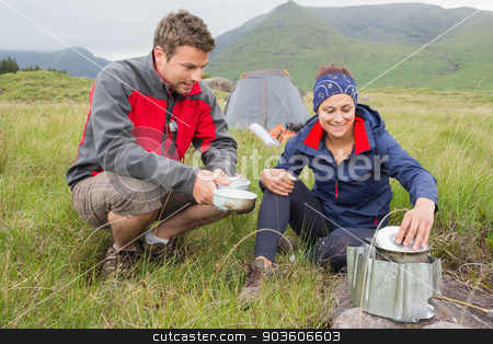 Couple cooking outside on camping trip stock photo, Couple cooking outside on camping trip in the wilderness by Wavebreak Media