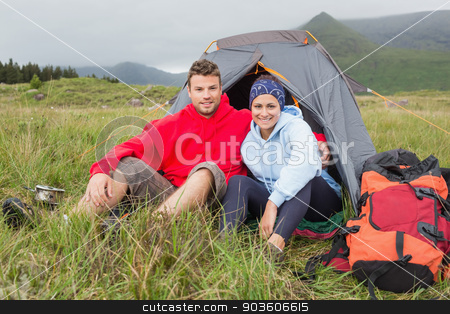 Couple on camping trip smiling at camera stock photo, Couple on camping trip smiling at camera outside their tent by Wavebreak Media