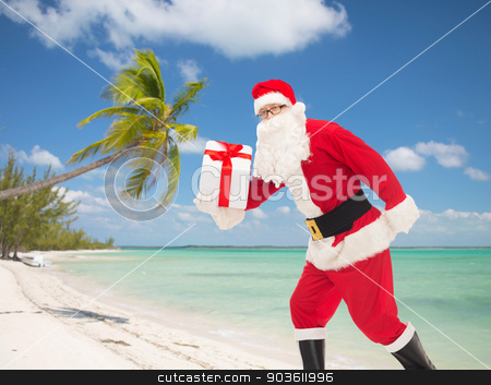man in costume of santa claus with gift box stock photo, christmas, holidays and people concept - man in costume of santa claus running with gift box over tropical beach background by Syda Productions