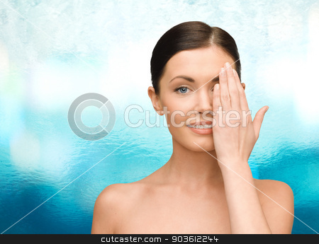smiling young woman covering face with hand stock photo, beauty, people and health concept - smiling young woman covering half of face with hand over blue glass background by Syda Productions