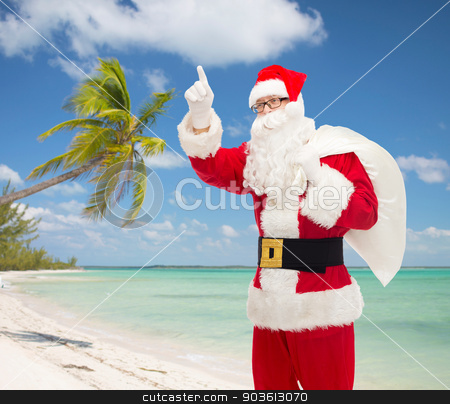 man in costume of santa claus with bag stock photo, christmas, holidays, gesture and people concept - man in costume of santa claus with bag pointing finger up over tropical beach background by Syda Productions