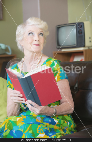 Grinning Woman with Book stock photo, Enchanted woman with grin reading a book by Scott Griessel