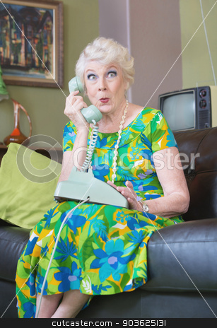 Curious Lady on Phone stock photo, Intrigued single senior female on rotary telephone by Scott Griessel