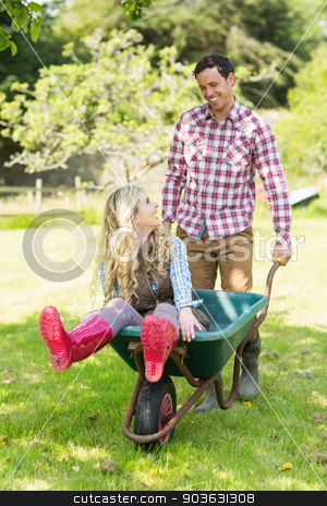 Happy man pushing his girlfriend in a wheelbarrow stock photo, Happy man pushing his girlfriend in a wheelbarrow in a sunny garden by Wavebreak Media