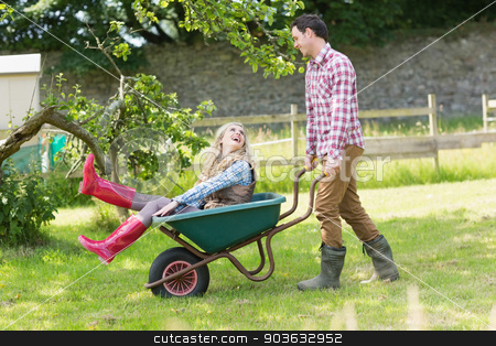Handsome man pushing his laughing girlfriend in a wheelbarrow stock photo, Handsome man pushing his laughing girlfriend in a wheelbarrow in a sunny garden by Wavebreak Media