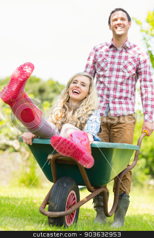 Smiling man pushing his laughing girlfriend in a wheelbarrow stock photo, Smiling man pushing his laughing girlfriend in a wheelbarrow in sunny garden by Wavebreak Media