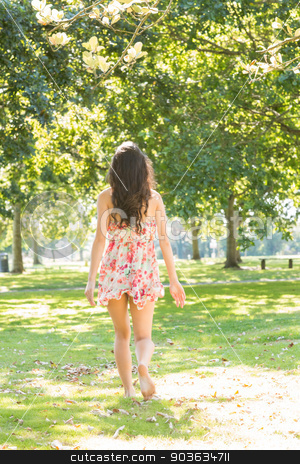 Rear view of stylish brunette walking on grass stock photo, Rear view of stylish brunette walking on grass in a park on a sunny day by Wavebreak Media