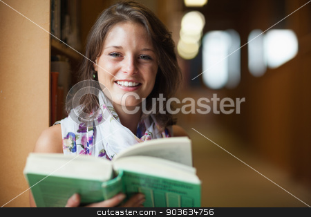 Close up of a smiling female student in library stock photo, Close up portrait of a smiling female student in the library by Wavebreak Media