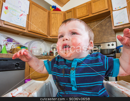 Grumpy Baby stock photo, Grumpy baby in kitchen is covered with food by Scott Griessel