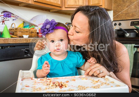Woman Kisses Baby in Kitchen stock photo, Woman in a messy kitchen kisses her baby by Scott Griessel