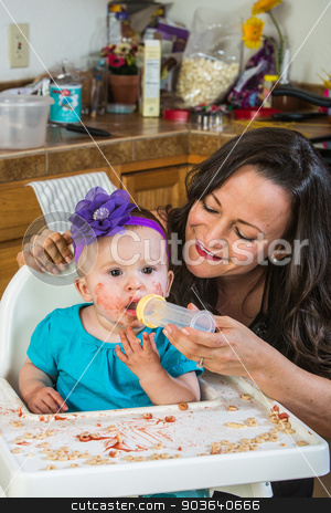 Woman Feeds Baby stock photo, A woman in the kitchen feeds her baby from bottle by Scott Griessel