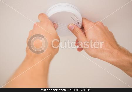 Handyman installing smoke detector stock photo, Handyman installing a smoke detector on the ceiling by Wavebreak Media