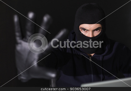 Hacker in balaclava gesturing and looking at camera stock photo, Hacker in balaclava gesturing and looking at camera on black background by Wavebreak Media