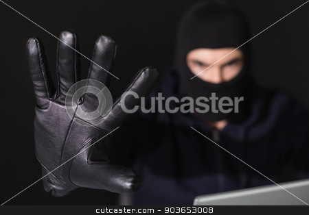 Hacker in balaclava with fingers spread out stock photo, Hacker in balaclava with fingers spread out on black background by Wavebreak Media