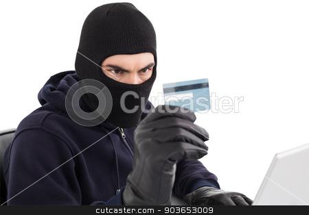 Burglar using credit card and laptop stock photo, Burglar using credit card and laptop on white background by Wavebreak Media