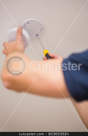Handyman installing smoke detector stock photo, Handyman installing smoke detector with screwdriver on the ceiling by Wavebreak Media