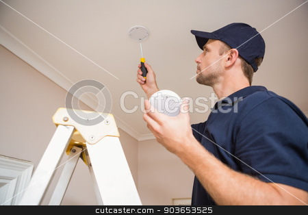Handyman installing smoke detector stock photo, Handyman installing smoke detector with screwdriver on the ceiling by Wavebreak Media