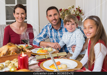 Portrait of smiling family during christmas dinner stock photo, Portrait of smiling family during christmas dinner at home in the living room by Wavebreak Media