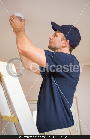 Handyman installing smoke detector stock photo, Focused handyman installing smoke detector with screwdriver on the ceiling by Wavebreak Media
