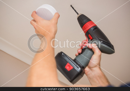 Handyman installing smoke detector stock photo, Handyman installing smoke detector with power tool on the ceiling by Wavebreak Media