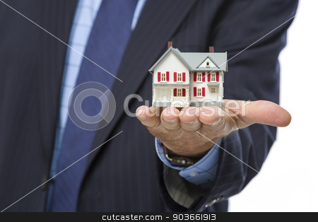 Male Real Estate Agent Holding Miniature House in Palm stock photo, Close Up of Male Real Estate Agent Holding Out A Miniature House in His Hand. by Andy Dean