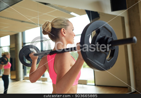 sporty woman exercising with barbell in gym stock photo, fitness, sport, powerlifting and people concept - sporty woman exercising with barbell in gym by Syda Productions