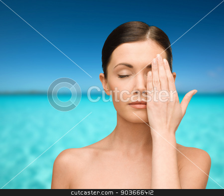 smiling young woman covering face with hand stock photo, beauty, people and health concept - smiling young woman covering half of face with hand over blue sky and sea background by Syda Productions