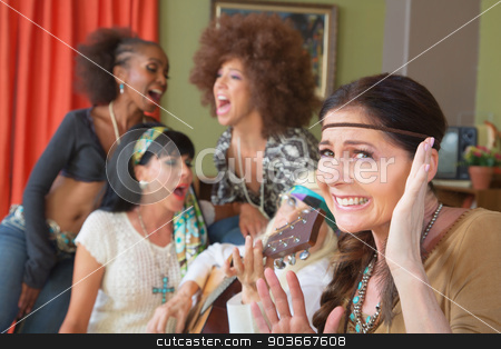 Cringing Woman and Singing Friends stock photo, Lady cringing as group of friends sing and play music by Scott Griessel
