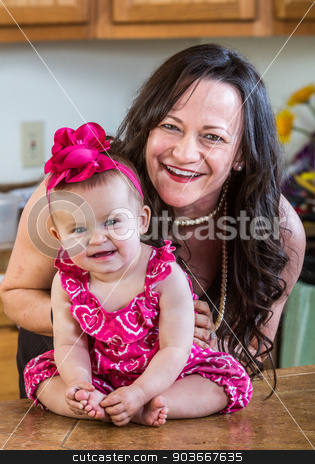 Mother Poses With Her Baby stock photo, A woman in the kitchen poses with her baby by Scott Griessel