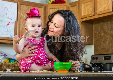 Mother Smiles at Baby stock photo, A mother in her kitchen smiles at her baby by Scott Griessel