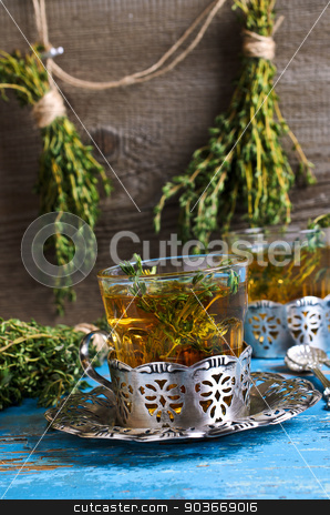Tea with thyme stock photo, Tea with thyme in a glass on old wooden boards of blue in rustic style by zia_shusha