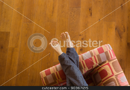 Mans legs on the couch stock photo, Mans legs on the couch at home in the living room by Wavebreak Media