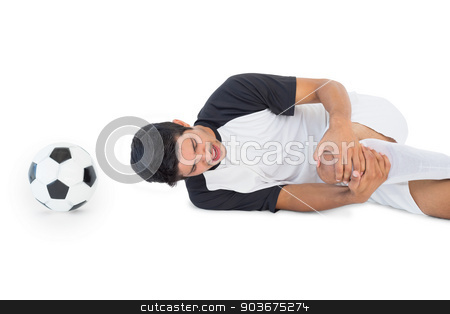 Soccer player lying down and shouting in pain stock photo, Side view of soccer player lying down and shouting in pain over white background by Wavebreak Media