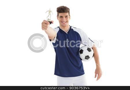 Football player holding winners trophy stock photo, Football player holding winners trophy over white background by Wavebreak Media