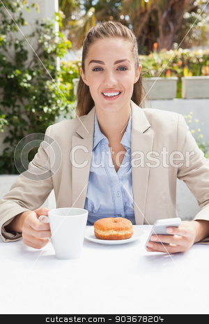 Beautiful businesswoman having a coffee and muffin stock photo, Beautiful businesswoman having a coffee and muffin outside at the coffee shop by Wavebreak Media