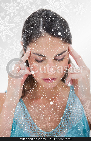 Portrait of a young woman having a headache stock photo, Portrait of a young woman having a headache against snowflakes on silver by Wavebreak Media