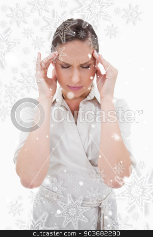 Portrait of a businesswoman having a headache stock photo, Portrait of a businesswoman having a headache against snowflakes by Wavebreak Media