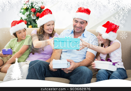 Composite image of family exchanging christmas gifts stock photo, Family exchanging Christmas gifts against fir tree forest and snowflakes by Wavebreak Media
