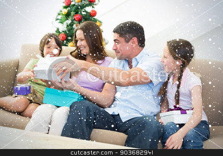 Composite image of family exchanging christmas presents stock photo, Composite image of Family exchanging Christmas presents against snow falling by Wavebreak Media