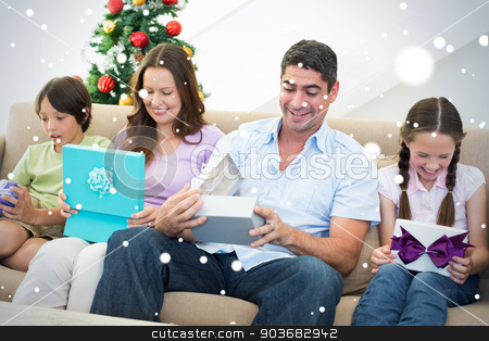 Composite image of family opening christmas gifts stock photo, Composite image of Family opening Christmas gifts against snow by Wavebreak Media