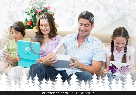 Composite image of family opening christmas gifts stock photo, Family opening Christmas gifts against fir tree forest and snowflakes by Wavebreak Media