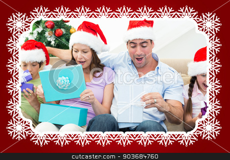 Composite image of family opening christmas presents stock photo, Composite image of family opening Christmas presents against snowflake frame by Wavebreak Media