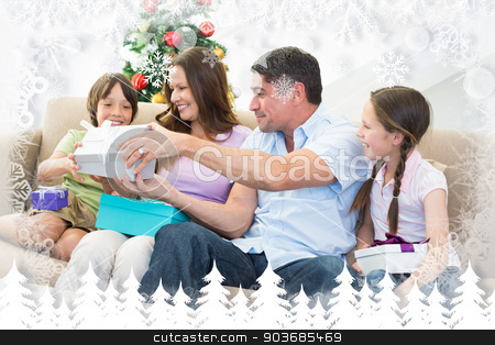 Composite image of family exchanging christmas presents stock photo, Family exchanging Christmas presents against fir tree forest and snowflakes by Wavebreak Media