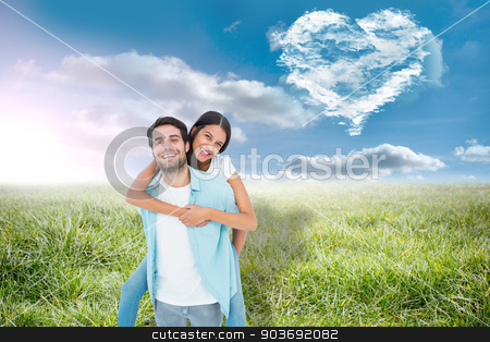Composite image of happy casual man giving pretty girlfriend pig stock photo, Happy casual man giving pretty girlfriend piggy back against cloud heart by Wavebreak Media
