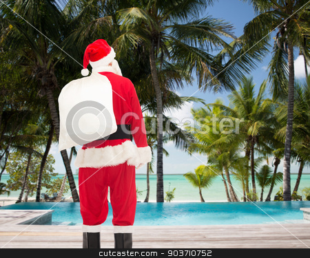 man in costume of santa claus with bag stock photo, christmas, holidays and people concept - man in costume of santa claus with bag from back over tropical beach and swimming pool background by Syda Productions