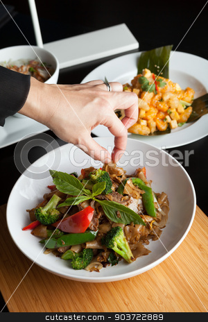 Food Stylist stock photo, Food stylist grooms a dish by adding sweet basil garnish to the traditional thai dish Pad Kee Mao drunken noodle. by Todd Arena