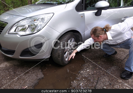 Upset driver man in front of automobile watching damaged car of  stock photo, Upset driver man in front of automobile watching damaged car of road full of cracked potholes in pavement by vladacanon1
