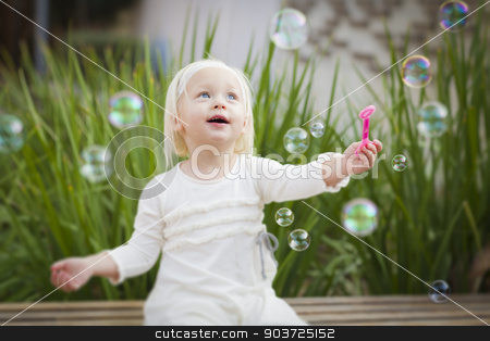 Adorable Little Girl Having Fun With Bubbles stock photo, Adorable Little Girl Sitting On Bench Having Fun With Bubbles Outside. by Andy Dean